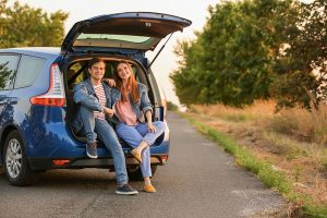 Couple sitting in the back of a hatchback car